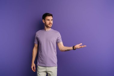 Positive handsome man standing with open arm while looking away on purple background stock vector