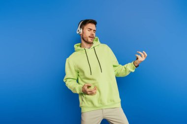 inspired young man in wireless headphones imitating playing guitar isolated on blue