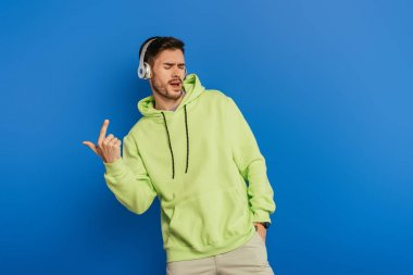 excited young man in wireless headphones singing with closed eyes on blue background