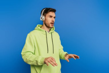 inspired young man in wireless headphones imitating playing piano isolated on blue