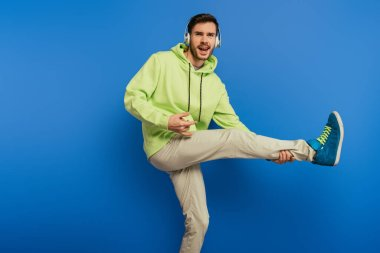 cheerful young man in wireless headphones dancing and singing on blue background