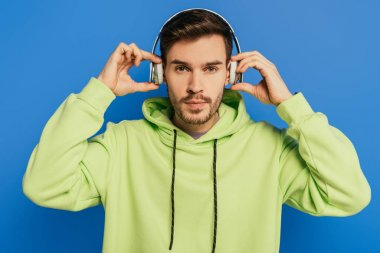 serious young man touching wireless headphones while looking at camera isolated on blue