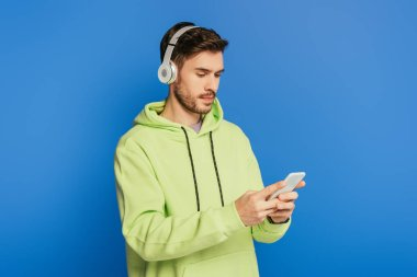attentive young man in wireless headphones using smartphone isolated on blue
