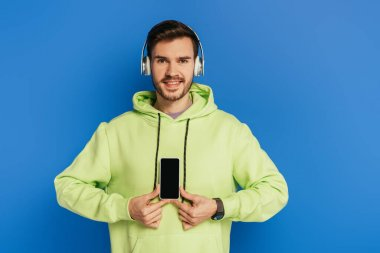 cheerful young man in wireless headphones showing smartphone with blank screen isolated on blue