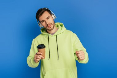dreamy young man in wireless headphones holding coffee to go and looking at camera on blue background