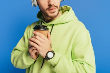 cropped view of young man in wireless headphones holding coffee to go isolated on blue