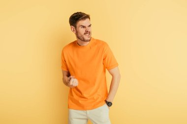 angry man grimacing and showing threatening gesture while looking away on yellow background