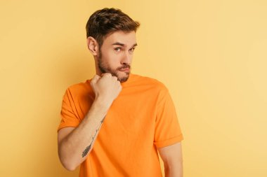 angry young man threatening while holding fist near jaw on yellow background