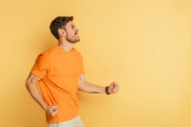 irritated young man showing threatening gesture and grimacing while looking up on yellow background