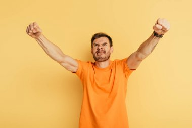 aggressive young man showing threatening gesture and grimacing while looking up on yellow background