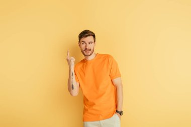 Tricky young man showing idea gesture on yellow background stock vector