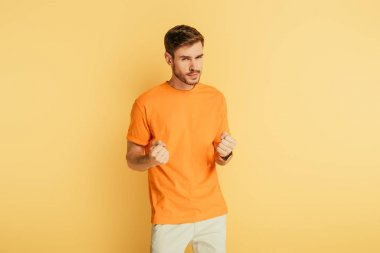 displeased, irritated young man showing fists while looking at camera on yellow background