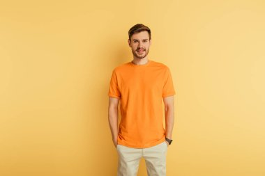 Smiling young man in orange t-shirt standing with hands in pockets on yellow background stock vector