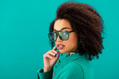 stylish african american woman in jacket looking at camera isolated on turquoise