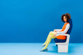 african american in retro dress sitting on seat on blue background