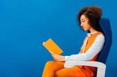 oldalnézetben afro amerikai retro ruha ül az ülésen, és olvasás könyv elszigetelt kék