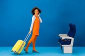 Fotografie usmívající se africký Američan v retro šaty chůze s cestovní taška na modrém pozadí