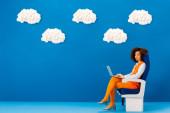 afro-amerikai retro ruha ül az ülésen, és tartsa laptop kék háttér felhők