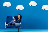 mosolygó afro-amerikai ül az üléseken, és használja a digitális tabletta kék alapon felhők