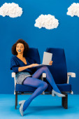 smiling african american sitting on seat and holdinglaptop on blue background with clouds