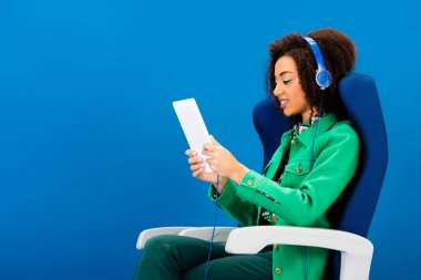 side view of smiling african american using digital tablet and listening to music isolated on blue