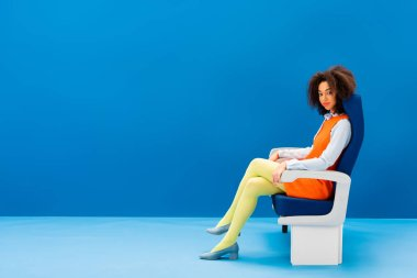 African american in retro dress sitting on seat on blue background stock vector