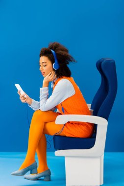 side view of african american in retro dress listening to music and using smartphone on blue background