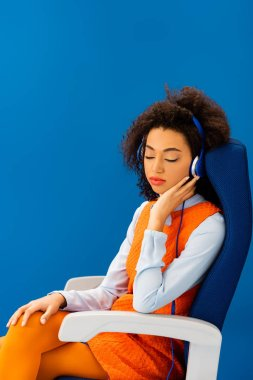 african american in retro dress listening to music and sleeping in seat isolated on blue