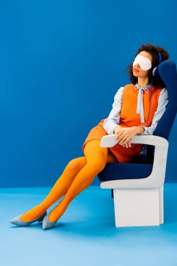 african american with sleeping mask listening to music and sleeping in seat on blue background