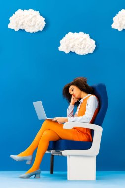 Bored african american in retro dress sitting on seat and looking at laptop on blue background with clouds stock vector