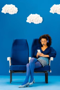 african american sitting on seat, listening to music and using smartphone on blue background with clouds