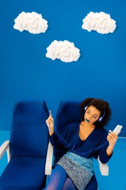 high angle view of african american sitting on seat, listening to music and holding smartphone on blue background with clouds