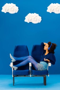side view of african american sitting on seats, listening to music on blue background with clouds