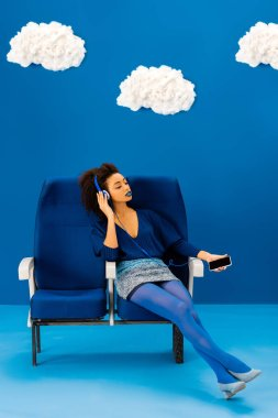 african american sitting on seat, listening to music and holding smartphone on blue background with clouds