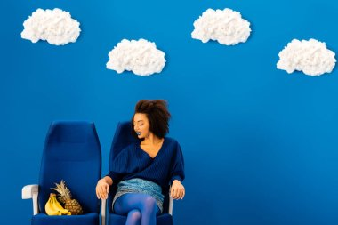 Smiling african american sitting on seat and looking at bananas and pineapple on blue background with clouds stock vector