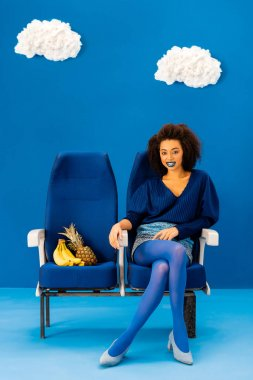 Smiling african american sitting on seat near bananas and pineapple on blue background with clouds stock vector