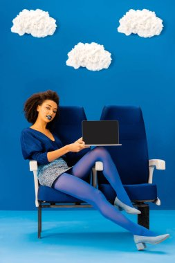 Smiling african american sitting on seat and holding laptop on blue background with clouds stock vector