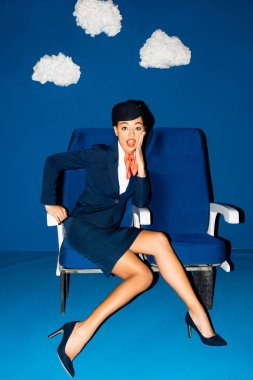 Shocked african american flight attendant sitting on seat on blue background with clouds stock vector