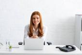 Erfolgreiche Geschäftsfrau lächelt in die Kamera neben Laptop und Handy auf dem Tisch