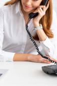 Vágott kilátás mosolygós üzletasszony beszél telefonon közelében laptop az asztalon
