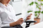 Fotografie Oříznutý pohled na podnikatelku pomocí digitálního tabletu v kanceláři