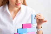 Fotografie Selective focus of businesswoman stacking colorful building blocks isolated on grey