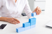 Selective focus of businesswoman stacking blue building blocks on table