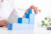Selective focus of businesswoman making marketing pyramid with blue building blocks near laptop on table