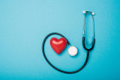Top view of decorative heart and stethoscope on blue background, world health day concept