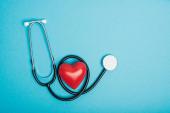 Horní pohled na dekorativní červené srdce se stetoskopem na modrém pozadí, koncept světového dne zdraví
