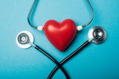 Top view of decorative heart with stethoscopes on blue background, world health day concept