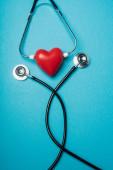 Horní pohled na dekorativní červené srdce s černým stetoskopem na modrém pozadí, koncept světového dne zdraví