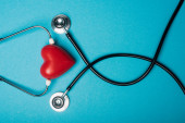 Top view of decorative red heart and black stethoscope on blue background, world health day concept