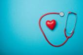 Horní pohled na dekorativní srdce a červený stetoskop na modrém pozadí, koncept světového dne zdraví